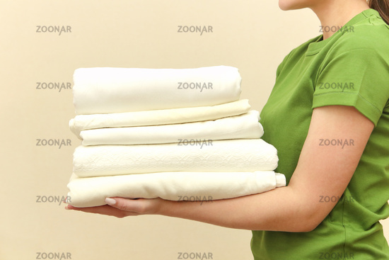 Young woman wearing green t-shirt holding towels in laundry room