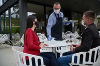 Waiter with protective medical mask and gloves serving guest