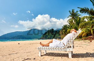 Man in white relaxing in sun bed on beach