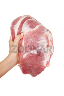 Female hand holding raw pork meat.