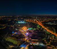 an impressive night view photo over Munich from the Olympic Tower at the ImPark festival at night with an illuminated ferris wheel.