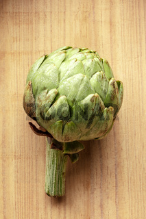 An overhead photo of a globe artichoke on a rustic wooden background