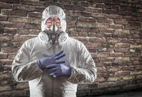 Chinese Man Wearing Hazmat Suit, Goggles and Gas Mask with Brick Wall Background
