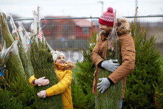 happy family buying christmas tree at market