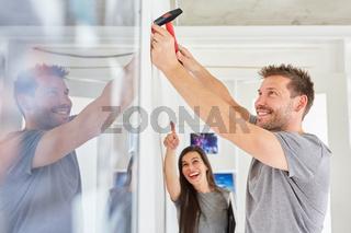 Junger Mann als Heimwerker mit einem Hammer