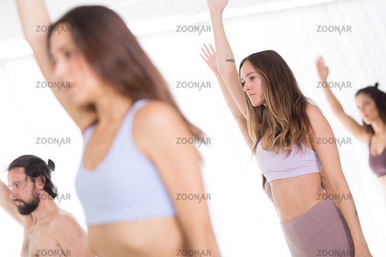 Group of young sporty attractive women in yoga studio, practicing yoga lesson with instructor, standing, stretching and relaxing after workout . Healthy active lifestyle, working out indoors in gym