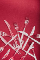Plastic cutlery scattered over red background