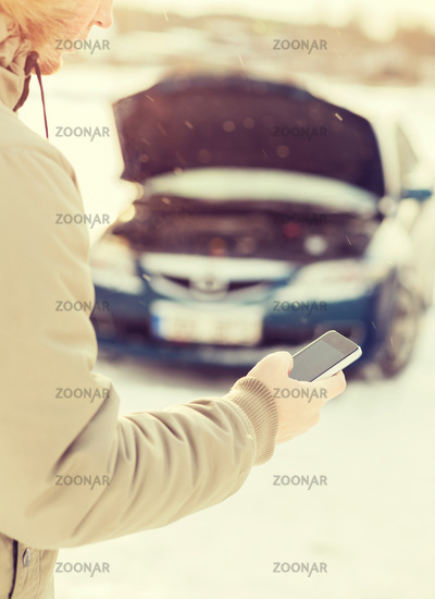 closeup of man with broken car and cell phone