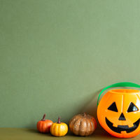 Halloween pumpkins on table with khaki green copy space