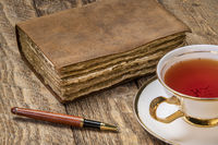 antique leatherbound journal with a cup of tea