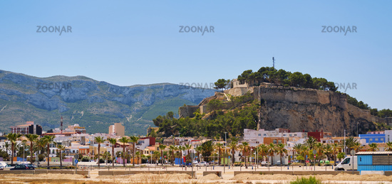 Panoramic photo on blue sky background ancient famous Denia Castle located on rocky hilltop mountain. Heart of ancient city, landmark and tourism concept. Alicante province, Costa Blanca, Spain