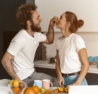 Boyfriend feeds or nursing his girlfriend. Beautiful young couple feeding each other making fun at modern kitchen and smiling while cooking at home