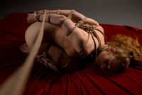 Slim blonde in the nude in shibari style portrait