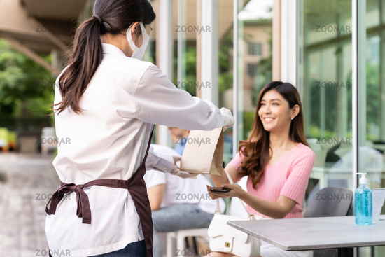 Customer pick up takeout food order from waitress