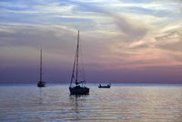 Sailboats anchored at sunset