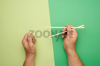 Pair of wooden chopsticks in a male hand on a green background