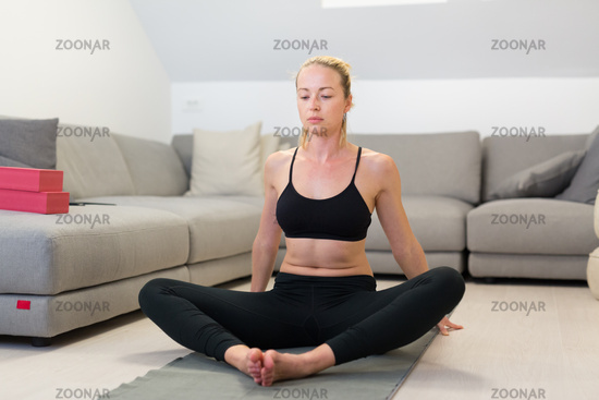 Beautiful blonde woman doing home workout indoors. Woman practice yoga at home. Fit girl using workout tutorials for healthy active lifestyle. Woman using quarantine for home workouts.