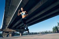 Sporty woman running outdoors under city bridge