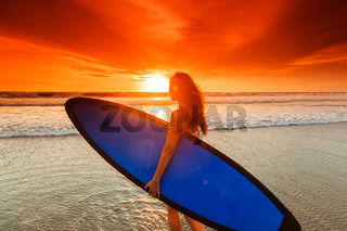 Woman on beach holding surfboard