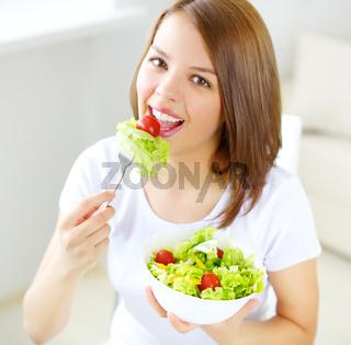 Teenager girl eating salad
