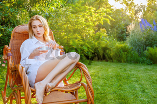 Young beautiful blonde woman relaxing alone at backyard garden during quarantine