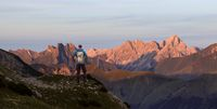Hiker Man standing at amazing view from high mountain to many other peaks at Sunset. Allgau, Bavaria, Alps, Germany.