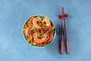 Noodles with shrimps and green peas, top shot with chopsticks