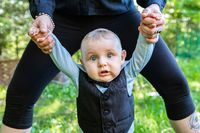Baby boy in formal dress holding parent hand