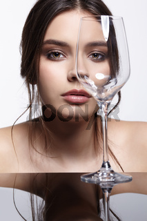 Girl hides her face behind wineglass. Beauty portrait of young woman at the mirror table.