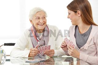 Seniorin spielt Karten mit Altenpflegerin