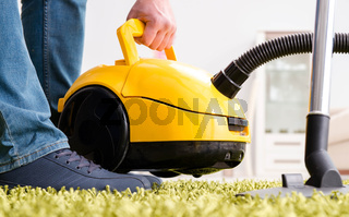 The man cleaning the floor carpet with a vacuum cleaner close up