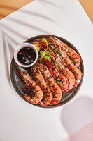 Prepared shrimps on plate on light background