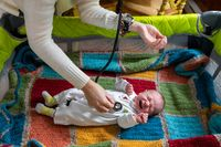 Doctor checking crying baby using stethoscope