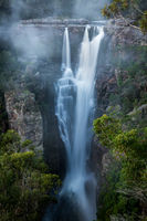 Enchanting Carrington Falls with wind blowing spray off waterfall