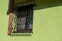 Cast Iron window grating with green wall
