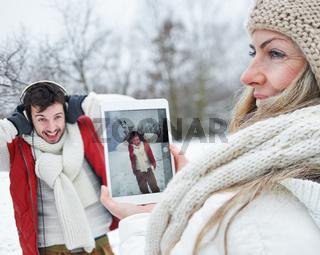 Paar im Winter macht Fotos mit Tablet PC