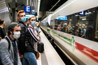 People wearing mask waiting for ICE train on platform at station( Berlin Hauptbahnhof)