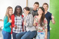 Schüler und Lehrer halten Daumen hoch