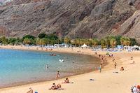 Tenerife, Spain - October 13, 2019: People sunbathing on sandy picturesque beach of Playa de Las Teresitas, enjoy views and warm weather and Atlantic  Ocean waters, Tenerife, Canary Islands, Spain