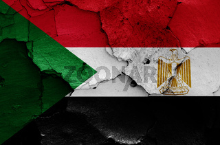 flags of Sudan and Egypt painted on cracked wall