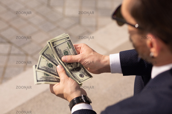 Close up of successful american businessman considering wad of 100 dollar banknotes while sitting on sidewalk. Rear view