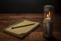 old journal and camping candle lantern burning