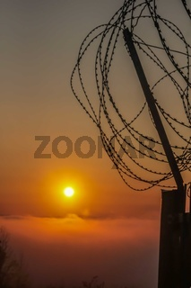 Sunrise on a foggy morning behind a barbed wire fence
