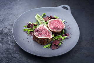 Fried dry aged beef fillet steak natural with vegetable fies and lettuce offered as close-up on a modern design plate