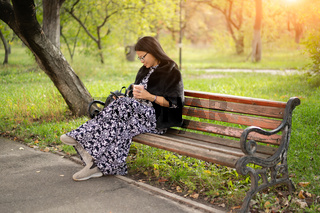 Woman of Asian ethnicity in beautiful long dress sits at park on old rusty bench and reads book using her gadget or checks social networks. Resting woman in sunny day outdoors