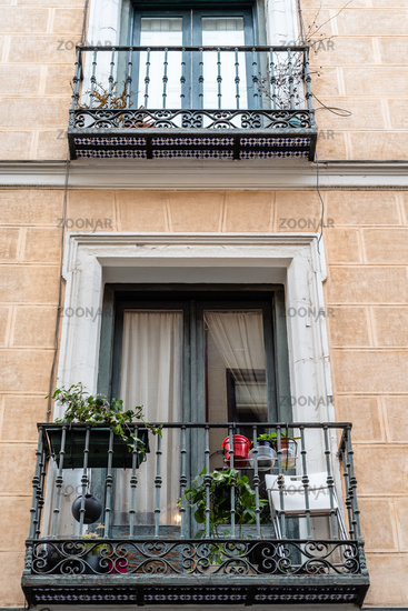 Low angle view of old cast iron balconies of old residential building in Lavapies quarter in Madrid