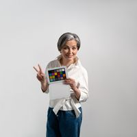Woman with gray hair keeps colorchecker on an isolated background. Adult woman smiles and shows two fingers. High quality photo
