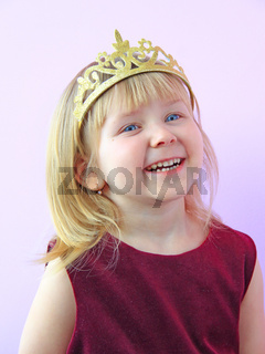 Little girl with crown on head smiling. Child in beautiful dress laughing