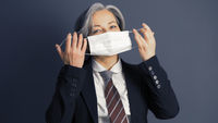 Mature business woman holding protective mask before her face. Quarantine concept