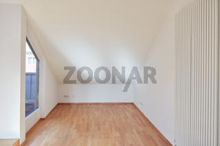 Leerer Raum mit Dachschräge in Dachgeschosswohnung